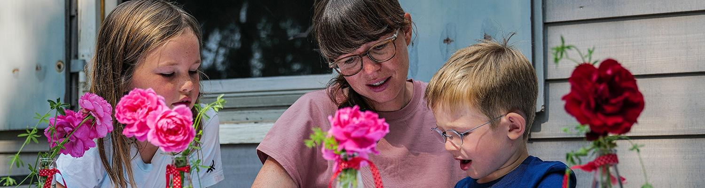 Eine Mutter die mit Ihren zwei Kindern vor dem Bauwagen vom Hofgut Willburger sitzen